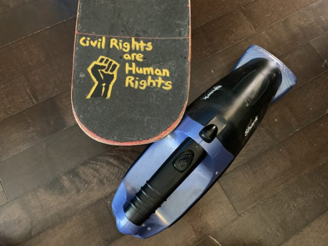 Skateboard tail with a BLM fist and the words 'Civil Rights are Human Rights' written on the griptape with yellow paint marker